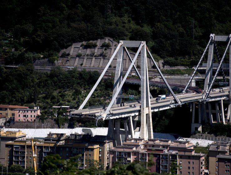 Può un ponte crollare nel silenzio? Erano le 11.36 del 14 agosto quando il Ponte Morandi cedette improvvisamente sul greto del torrente Polcevera, causando la morte di 43 persone. I video che ripresero in diretta la tragedia avevano tutti un elemento comune: il viadotto sembrava crollare senza emettere alcun suono, le tonnellate di macerie sembravano svanire nel silenzio sotto l'acquazzone di quella vigilia di Ferragosto. Lo stesso silenzio surreale che il 14 settembre, alle 11.36, unì una città intera. Ad un mese esatto dall'accaduto, i negozianti abbassarono le saracinesche, gli impiegati abbandonarono gli uffici, tutti i genovesi scesero in strada e si fermarono per un minuto di silenzio. -video Genova 14 settembre- A 168 giorni dal crollo, l'8 febbraio, sono partiti i lavori di demolizione di ciò che rimane del ponte Morandi. La rimozione del moncone ovest rappresenta il primo passo verso l'inizio dei lavori e per questo sono presenti il Presidente del Consiglio Giuseppe Conte, il ministro delle Infrastrutture e dei Trasporti Danilo Toninelli, il governatore ligure e commissario per l'emergenza Giovanni Toti e il sindaco di Genova, nonché commissario per la ricostruzione del viadotto sul Polcevera, Marco Bucci. La timeline La nomina del Commissario straordinario alla ricostruzione Quale sarà il tratto distintivo del suo mandato? «Avere un ponte». Con queste parole Marco Bucci, sindaco di Genova, si presentò come Commissario straordinario alla ricostruzione del Ponte Morandi. Il sindaco di Genova è stato nominato il 4 ottobre 2018 dal Premier Giuseppe Conte. I poteri del Commissario sono quasi illimitati, l'unico limite stabilito dalla Camera è infatti il rispetto del Codice Antimafia. Il reperto 132 La svolta delle indagini riguardanti la causa del cedimento arrivò il 19 ottobre 2018. La procura catalogò il reperto 132, uno strallo di cemento armato che mostrò un avanzato stato di corrosione dei cavi d'acciaio interni. Questa sarebbe la riprova del fatto che il 